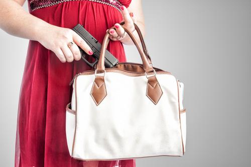 Woman taking pistol from her handbag Stock Photo