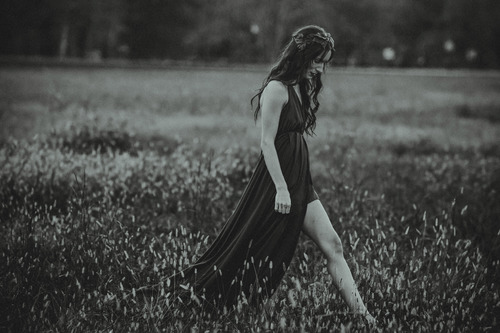 Woman walking in field black and white photo Stock Photo