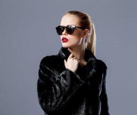 Woman wearing sunglasses wearing black fur coat Stock Photo