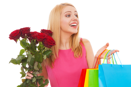 Young beauty holding shopping bags and flowers Stock Photo