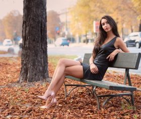 Beautiful woman sitting on a park bench Stock Photo