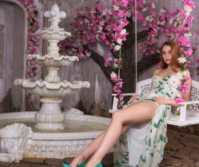 Beautiful woman sitting on swing posing Stock Photo