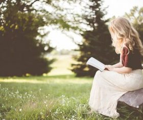Blonde girl reading book in the park Stock Photo