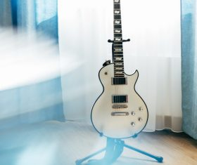 Electric guitar in the corner of the room Stock Photo
