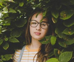 Girl hidden among the green leaves Stock Photo