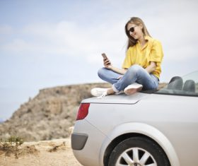 Girl sitting on the top of the car looks at the phone Stock Photo