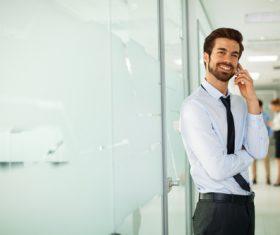 Man standing in the company corridor using phone Stock Photo 01