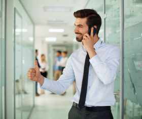 Man standing in the company corridor using phone Stock Photo 02