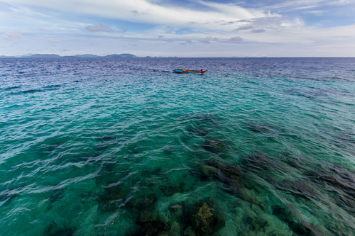 Small fishing boat floating on the sea Stock Photo