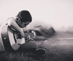 Stock Photo Little boy playing guitar