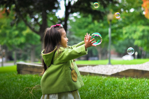 Stock Photo Little girl catching bubbles