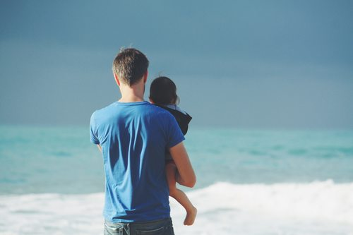 Stock Photo Man holding daughter watching the sea