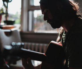 Stock Photo Man playing guitar at home