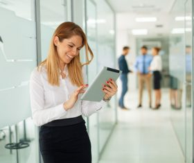 Stock Photo Woman standing in the hallway using tablet