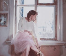 Woman sitting on the window sill with bow Stock Photo