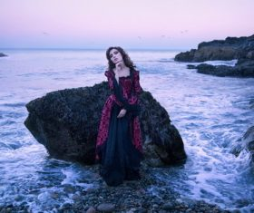 Woman standing next to rock by the sea Stock Photo