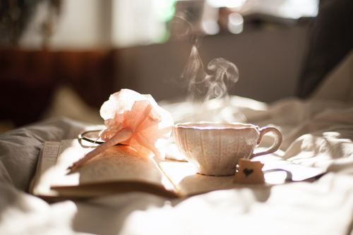 a cup of hot drink on the book Stock Photo