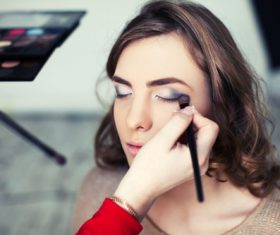 Beautician draws eye shadow on model Stock Photo
