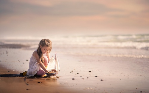Cute little girl playing with boat model Stock Photo