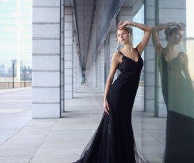 Female model wearing black long skirt taking pictures outdoors Stock Photo