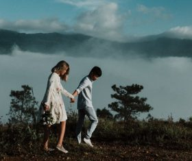 Lovers walking hand in hand on the mountain Stock Photo