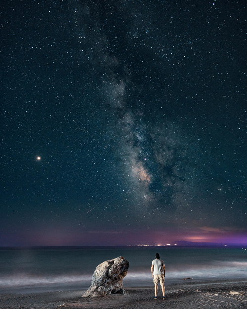 Man looking up at the starry sky Stock Photo