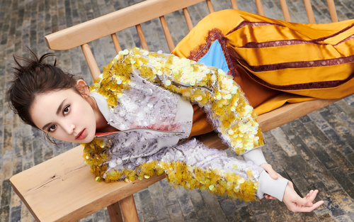 Pretty girl in fashionable clothes lying on wooden chair Stock Photo