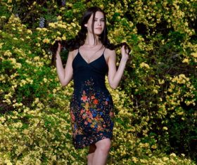 Slim fit beautiful girl and yellow flowering shrubs background Stock Photo