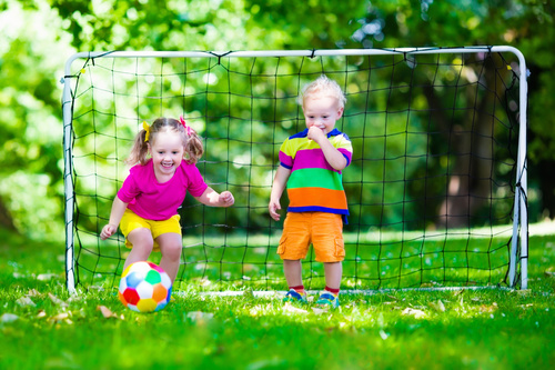 Two little kids playing football Stock Photo