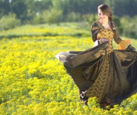Woman dancing in yellow flower field Stock Photo