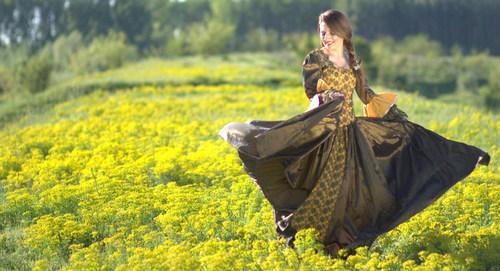 Woman dancing in yellow flower field Stock Photo