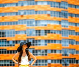 Woman in front of orange building Stock Photo