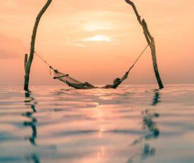 Woman lying in hammock in the sea Stock Photo