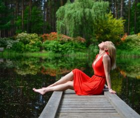 Woman sitting on the wooden bridge enjoying the natural air Stock Photo
