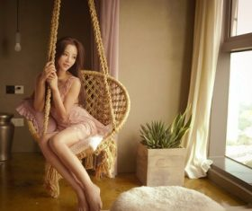 Beautiful girl sitting in hanging chair Stock Photo