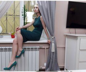 Beautiful woman sitting on the windowsill posing Stock Photo