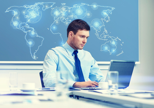 Businessman using laptop to contact global customers Stock Photo