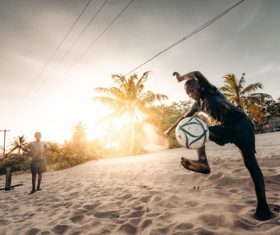 Children playing football on the beach Stock Photo