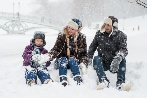 Family of three playing in the snow Stock Photo