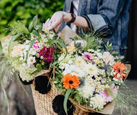 Girl carrying a basket full of flowers Stock Photo 02