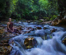 Monk sitting next to the stream meditating Stock Photo