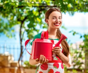 Smiling woman holding a spray pot Stock Photo