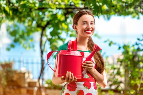 Smiling woman holding a spray pot Stock Photo