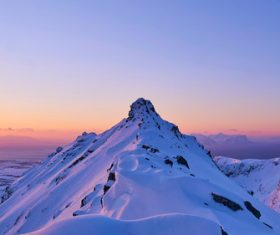 Snowy Mountain Peak with Sunrise Glow Stock Photo