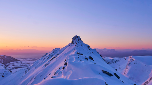 Snowy Mountain Peak with Sunrise Glow Stock Photo