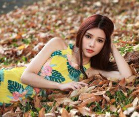 Stock Photo Girl posing outdoors lying on fallen leaves in autumn
