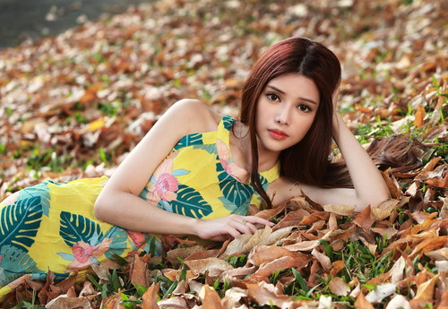Stock Photo Girl posing outdoors lying on fallen leaves in autumn
