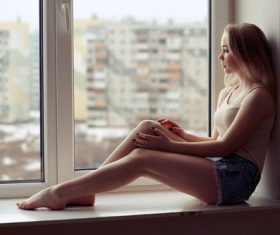 Stock Photo Girl sitting on the window sill and looking out the window