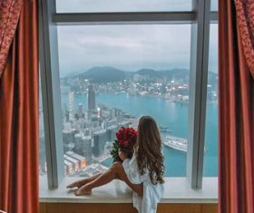 Stock Photo Girl sitting on the window sill holding rose
