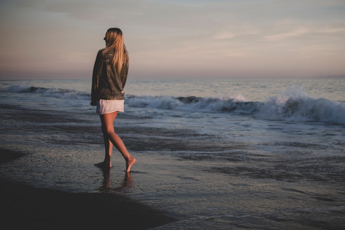 Stock Photo Girl walking on the beach back shadow